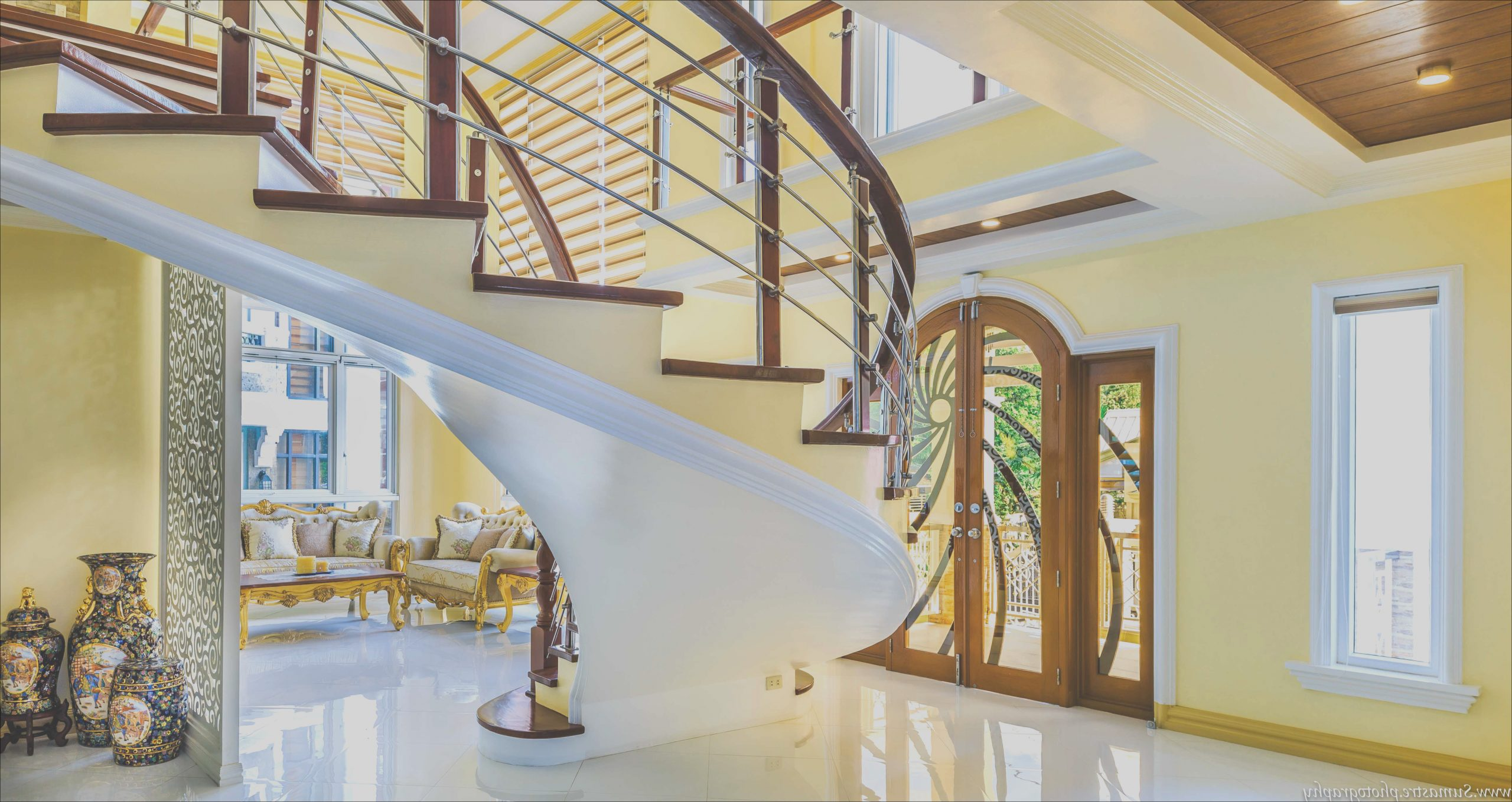 gold toned mansion with basement stairs going to living room architectural and interior design photography
