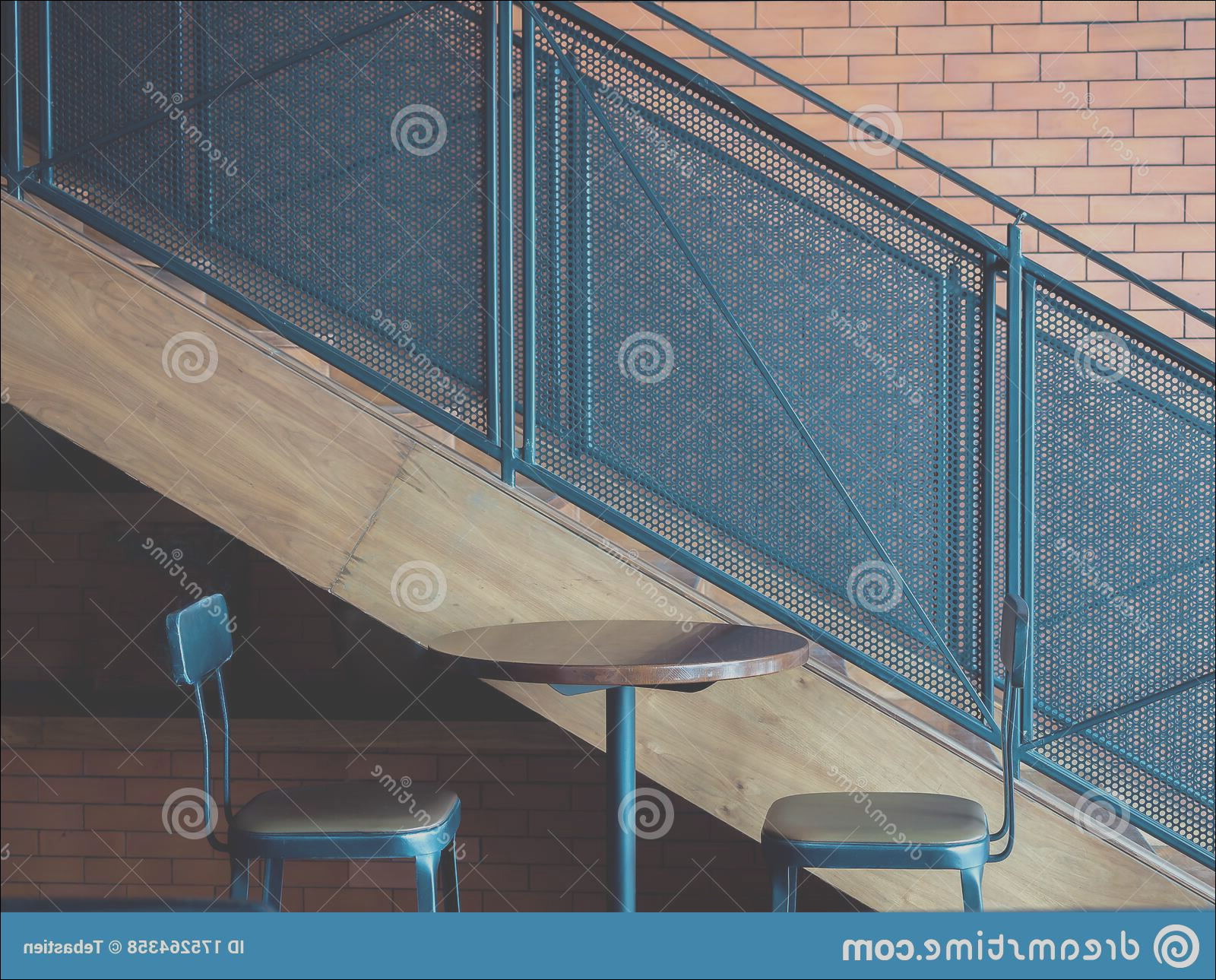 cafe decoration design round wooden table two modern bar stools near metal stairs brick wall background empty image